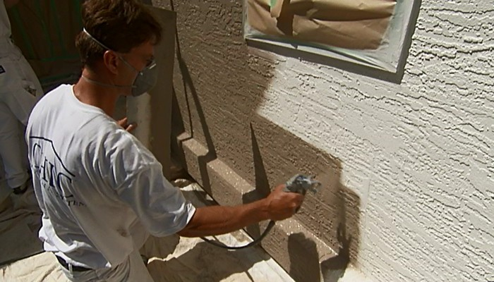 Installer applying stucco coating by spraying exterior