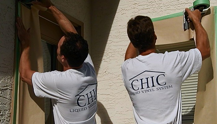 Installers preparing exterior for stucco coating application